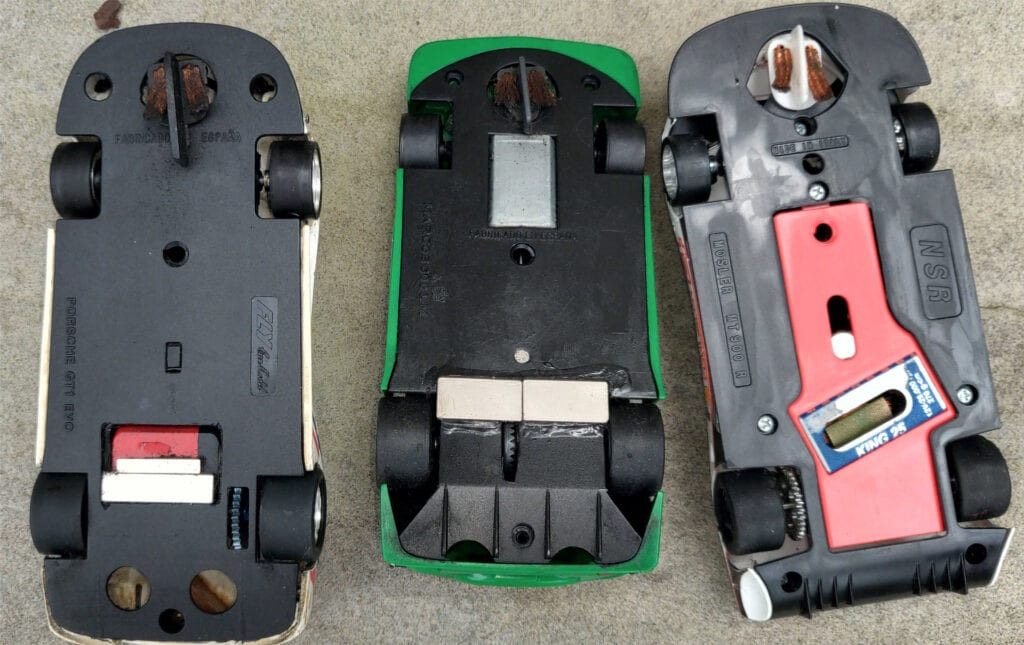 A variety of slot cars with One G slot car rule magnet setups.